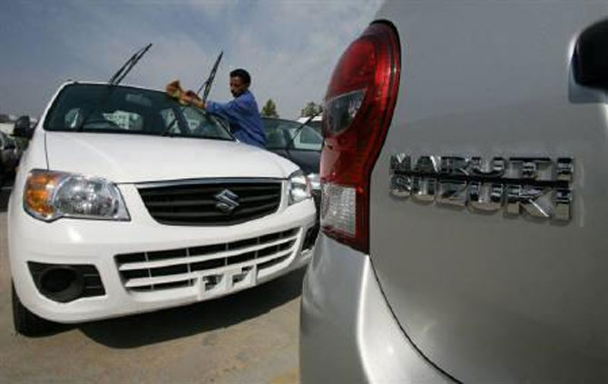 A worker cleans a parked car at the Maruti Suzuki's stockyard.