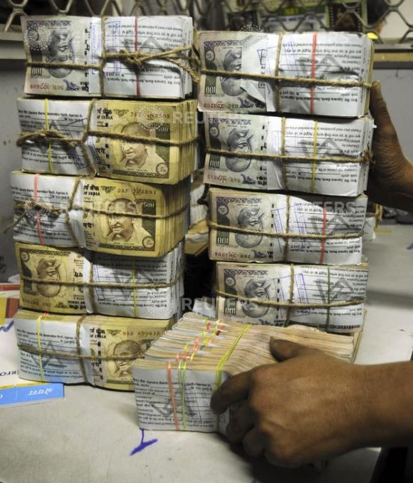 An employee counts bundles of Indian currency notes inside a bank.