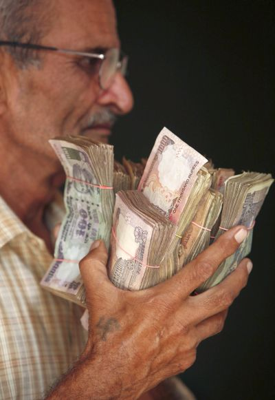 A man holds currency notes near a cash counter after withdrawing them inside a bank on the outskirts of Jammu.
