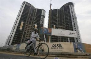 A passerby cycling in front of an under-construction building by DLF