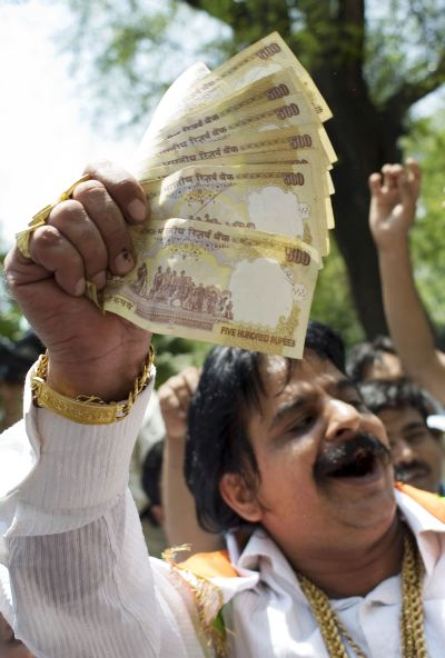 A man hands out money as supporters celebrate election results in front of the headquarters of the Congress Party.