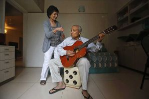 Aruna, 81, watches as her husband Vidyadhar Gokhale, 84, play guitar in their flat at the Athashri retirement village in Baner, on the outskirts of Pune.