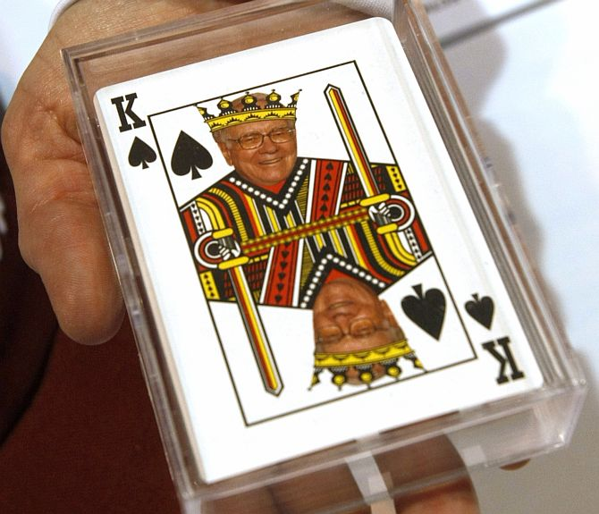 A woman displays playing cards for sale with a picture of Berkshire Hathaway Chairman Warren Buffett as the king of spades at a souvenir stand at the company trade show during the BH annual meeting in Omaha.
