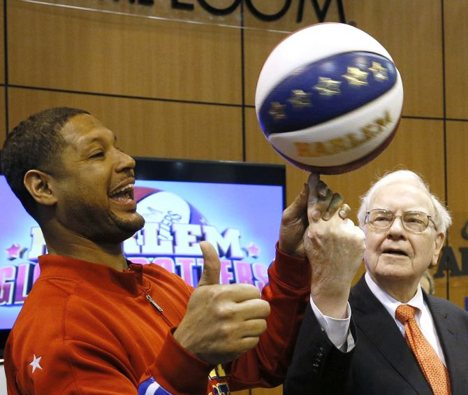 Berkshire Hathaway CEO Warren Buffett spins a basketball on his fingertip with the help of Harlem Globetrotter member Handles Franklin just before the company's annual meeting in Omaha.