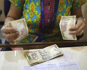 A cashier counts rupees inside a bank in Mumbai. Photograph: Danish Siddiqui/Reuters