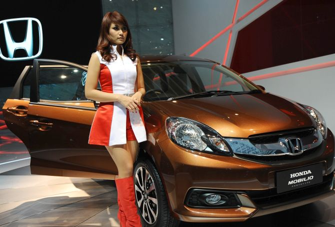 A model stands next to Honda Mobilio prototype on display at The 21st Indonesia International Motor Show.