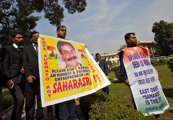 Supporters of the Sahara group chairman Subrata Roy holds banners in the premises of the Supreme Court as Roy appeared in the court.
