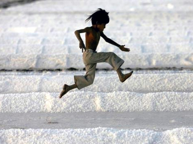 A worker's son plays in a salt pan near Bhavnagar in Gujarat.