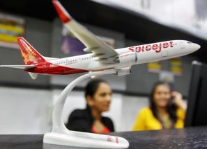 Employees at a travel agency office working besides a model of a SpiceJet aircraft.