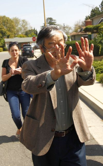 A man widely believed to be Bitcoin currency founder Satoshi Nakamoto is surrounded by reporters as he leaves his home in Temple City, California.