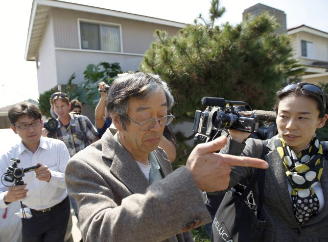 Satoshi Nakamoto is surrounded by reporters.
