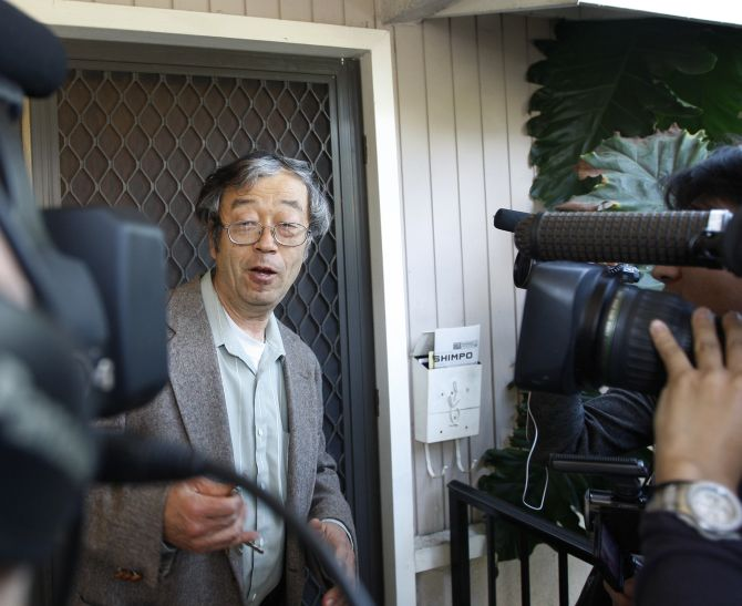 A man widely believed to be Bitcoin currency founder Satoshi Nakamoto is surrounded by reporters as he leaves his home in Temple City.