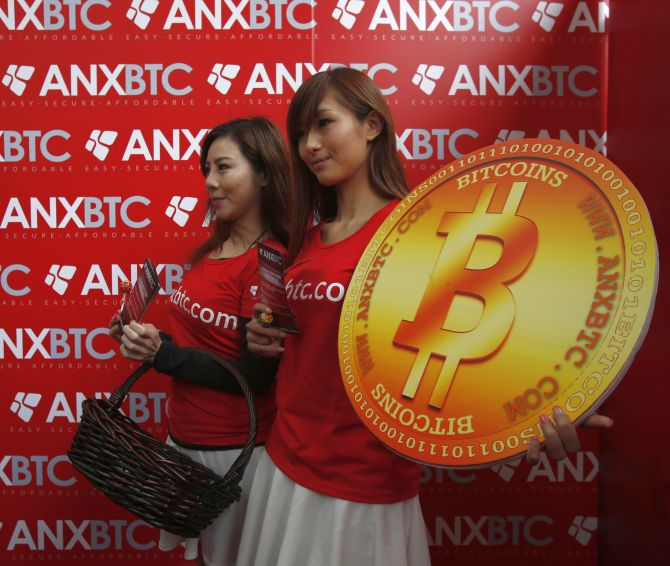 Attendants pose with a bitcoin sign during the opening of Hong Kong's first bitcoin retail store.