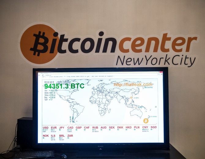 A television screen displays various bitcoin rates at Bitcoin Center NYC.