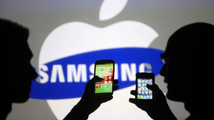 Men are silhouetted against a video screen with Apple and Samsung logos.