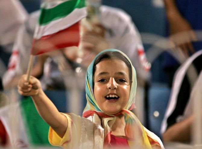An girl waves an Iranian flag during a football game between Iran against Oman in the in Jeddah, Saudi Arabia.
