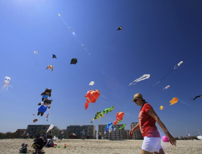 A woman strolls on the beach during Romania's first international Black Sea Kite Festival at the Black Sea resort of Mamaia, about 260 km (162 miles) east of Bucharest.