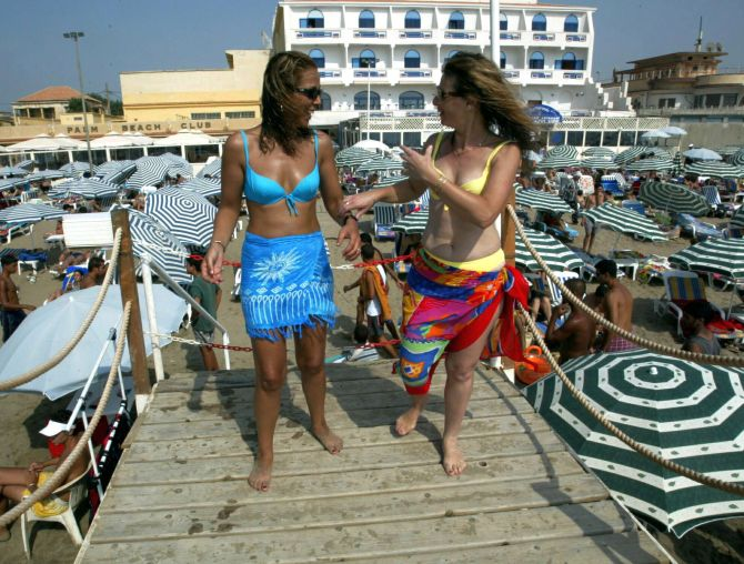 Women walk along a jetty in bikinis at the Palm Beach Club in Algiers.