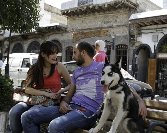 Syrian Christians sit in a park in Bab Touma, a Christian quarter of the Old City in Damascus.