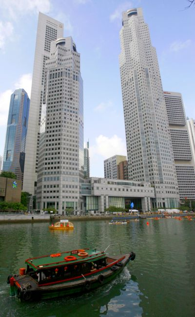 A boat on the Singapore river sails past office buildings in Singapore.