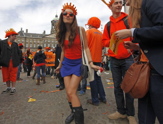 A woman celebrates the new Dutch King Willem-Alexander who succeeds his mother Queen Beatrix, in Amsterdam's Dam Square.