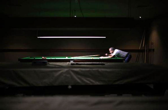 A member of the Shell Club, a sports and social venue, plays at a pool table near the Shell Oil refinery in Geelong.