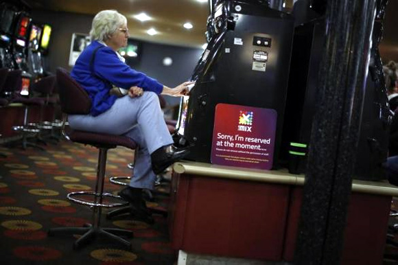 A visitor to the Shell Club, a sports and social venue, plays a slot machine near the Shell Oil refinery in Geelong.