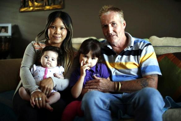 Alcoa aluminium smelter worker Ian Heinrich, 51, poses for a photograph with his wife Wayan and daughters Jessica, 4, and Jayla, 3 months.
