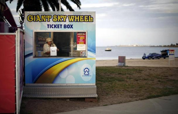 A worker at a beach-front attraction, the Giant Sky Wheel, goes on a break at