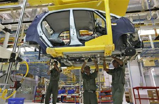 Employees work inside the plant for the Tata Nano car at Sanand in Gujarat June 2, 2010