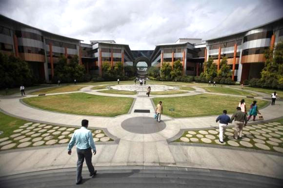 Employees walk in a forecourt at the Infosys campus in the Electronic City area of Bengaluru.
