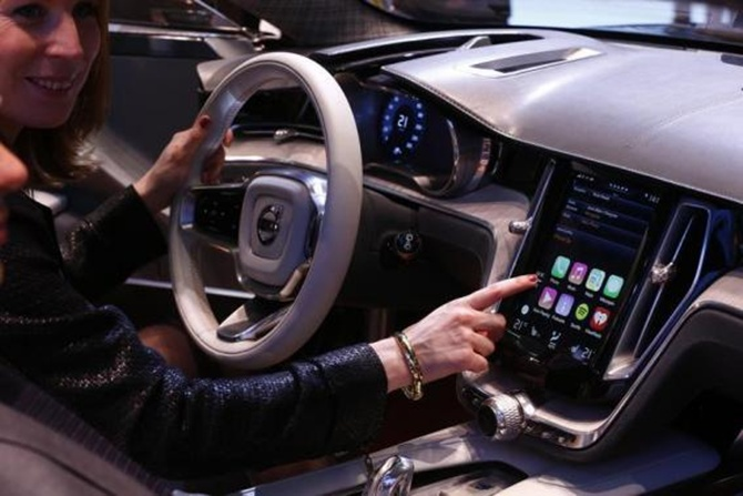 A woman touches the display inside a Volvo car.