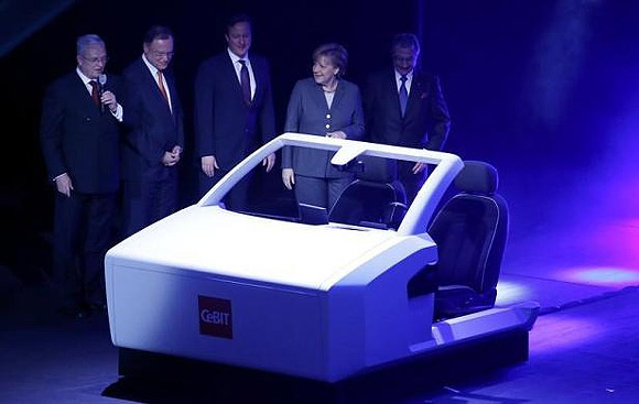 Volkswagen Chief Executive Martin Winterkorn, Prime Minister of Lower Saxony Stephan Weil, British Prime Minister David Cameron, German Chancellor Angela Merkel and President of the German Association for Information Technology, Telecommunications and New Media BITCOM Dieter Kempf look at a model of a car which drives itself.