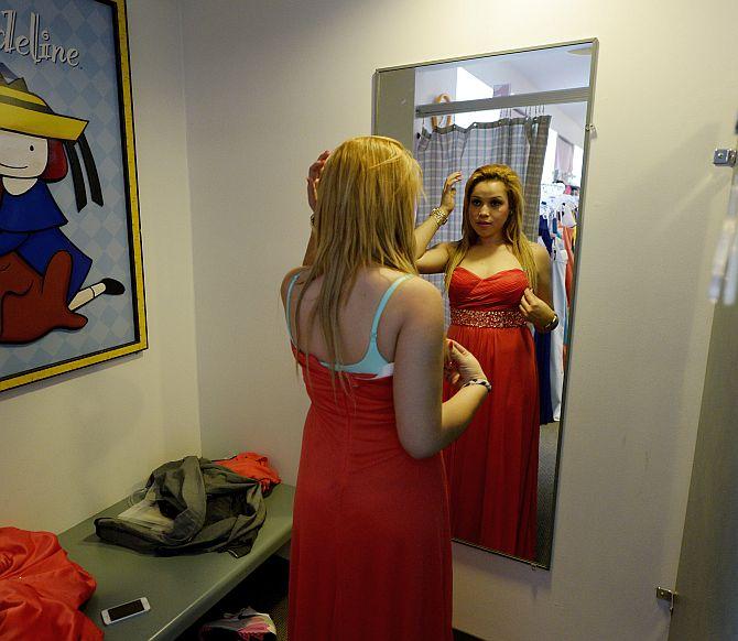 Marta Cruz, 17, from Helen Bernstein High School tries a prom gown.