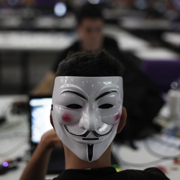 A man wearing a Guy Fawkes mask surfs the web.