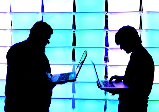 Participant hold their laptops in front of an illuminated wall.