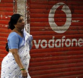 A woman walks past a large logo of Vodafone displayed on a shop in Mumbai