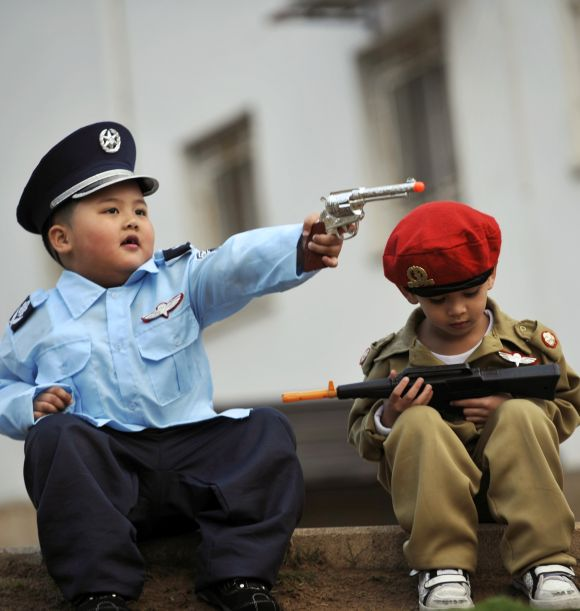 Children dressed in costume sit together during a party celebrating.