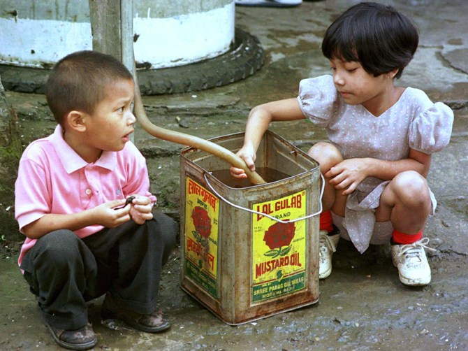 Children fill a cannister with drinking water from a public tap in Aizawl.