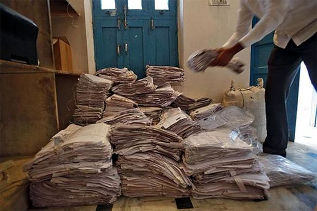A person arranges the Unique Identification documents submitted by people for their enrolment in Rajasthan.
