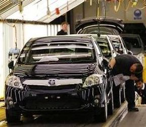 A worker inspecting cars at the Toyota factory.