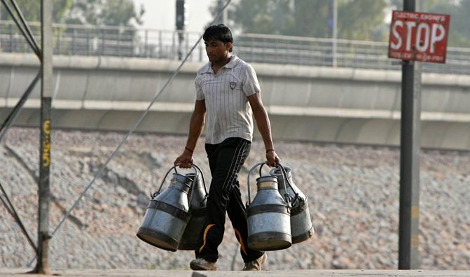 A milkman carries empty milk containers at a railway platform in New Delhi