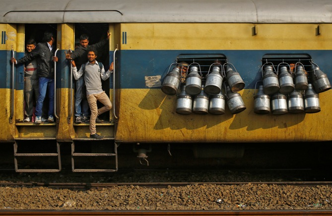 Commuters stand on the door of a passenger train as milk containers hang on the windows in Ghaziabad.