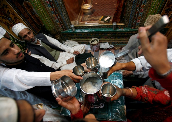 A man distributes milk among Kashmiri Muslims before they break their day-long fast inside a Sufi shrine during Ramadan in Srinagar.