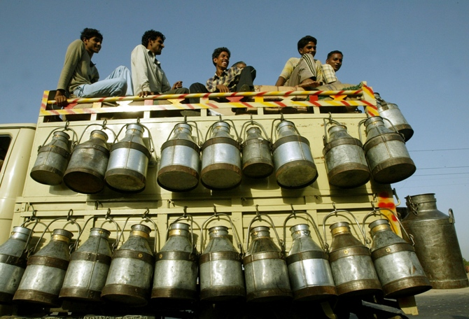 Milkmen sit on top of a truck with milk containers in New Delhi.