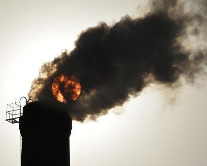 The sun is seen behind smoke billowing from a chimney of a heating plant in Taiyuan, Shanxi province.