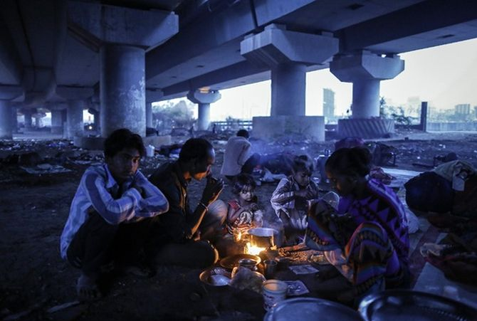 A migrant family prepares food below a flyover in Mumbai.