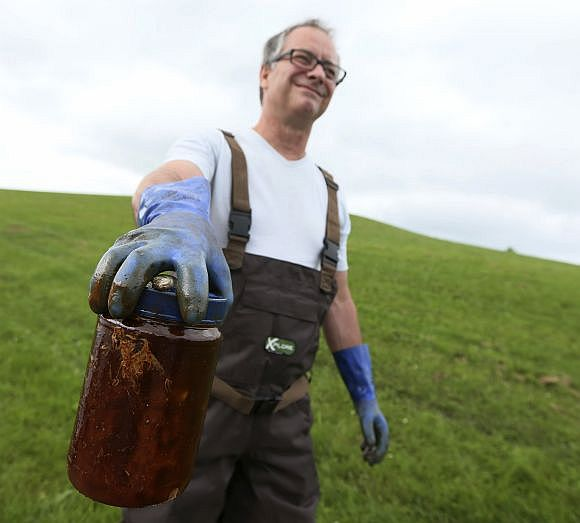 Denis Nadeau from Quebec holds crude oil in a jar.