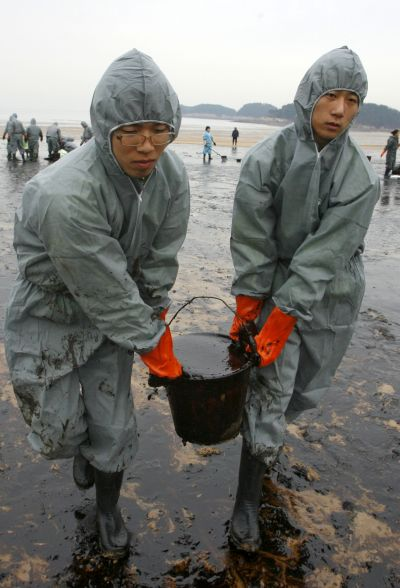 Soldiers from the South Korean army carry a bucket filled with oil.