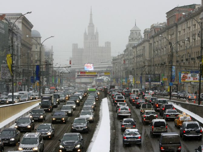 Cars move under a snowfall in central Moscow.